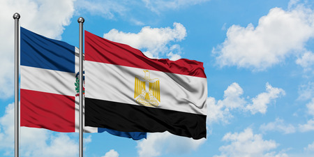Dominican Republic and Egypt flag waving in the wind against white cloudy blue sky together. Diplomacy concept, international relations.
