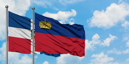 Dominican Republic and Liechtenstein flag waving in the wind against white cloudy blue sky together. Diplomacy concept, international relations.