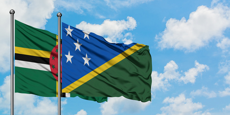 Dominica and Solomon Islands flag waving in the wind against white cloudy blue sky together. Diplomacy concept, international relations. Stok Fotoğraf