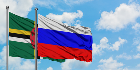Dominica and Russia flag waving in the wind against white cloudy blue sky together. Diplomacy concept, international relations.