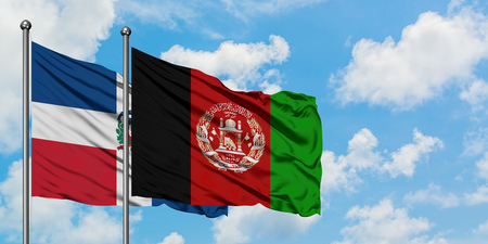 Dominican Republic and Afghanistan flag waving in the wind against white cloudy blue sky together. Diplomacy concept, international relations. 写真素材