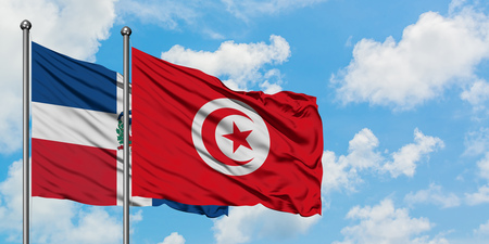 Dominican Republic and Tunisia flag waving in the wind against white cloudy blue sky together. Diplomacy concept, international relations.