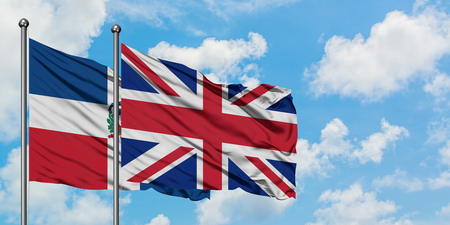 Dominican Republic and United Kingdom flag waving in the wind against white cloudy blue sky together. Diplomacy concept, international relations.