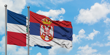 Dominican Republic and Serbia flag waving in the wind against white cloudy blue sky together. Diplomacy concept, international relations.