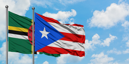Dominica and Puerto Rico flag waving in the wind against white cloudy blue sky together. Diplomacy concept, international relations. 스톡 콘텐츠