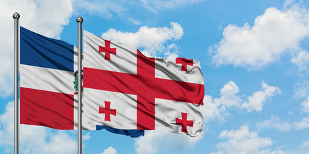 Dominican Republic and Georgia flag waving in the wind against white cloudy blue sky together. Diplomacy concept, international relations.