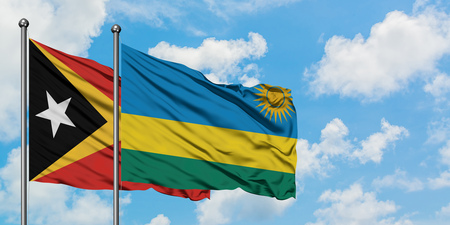 East Timor and Rwanda flag waving in the wind against white cloudy blue sky together. Diplomacy concept, international relations.
