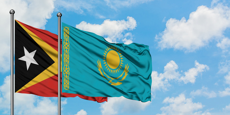 East Timor and Kazakhstan flag waving in the wind against white cloudy blue sky together. Diplomacy concept, international relations.