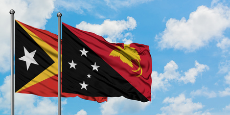 East Timor and Papua New Guinea flag waving in the wind against white cloudy blue sky together. Diplomacy concept, international relations.