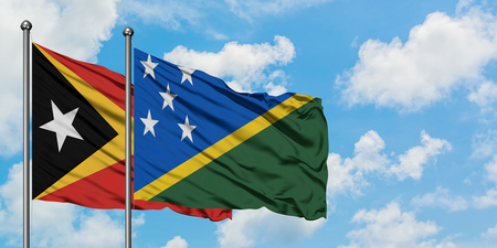 East Timor and Solomon Islands flag waving in the wind against white cloudy blue sky together. Diplomacy concept, international relations. Stok Fotoğraf