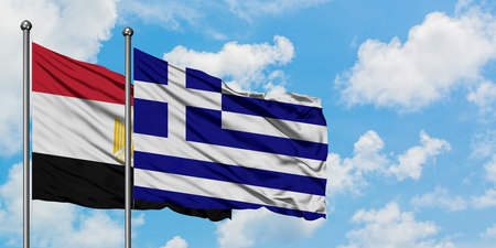 Egypt and Greece flag waving in the wind against white cloudy blue sky together. Diplomacy concept, international relations.