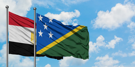 Egypt and Solomon Islands flag waving in the wind against white cloudy blue sky together. Diplomacy concept, international relations.