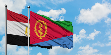 Egypt and Eritrea flag waving in the wind against white cloudy blue sky together. Diplomacy concept, international relations. Stok Fotoğraf