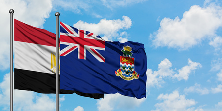 Egypt and Cayman Islands flag waving in the wind against white cloudy blue sky together. Diplomacy concept, international relations.