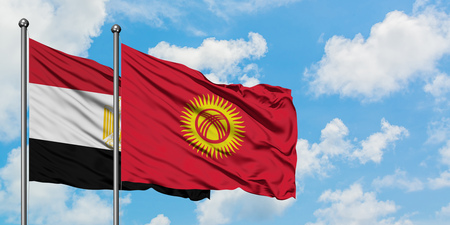 Egypt and Kyrgyzstan flag waving in the wind against white cloudy blue sky together. Diplomacy concept, international relations. Stok Fotoğraf