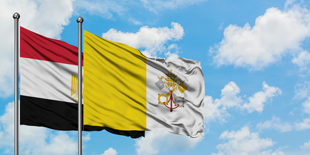 Egypt and Vatican City flag waving in the wind against white cloudy blue sky together. Diplomacy concept, international relations.
