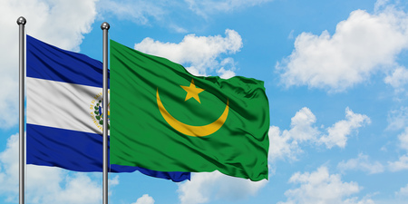 El Salvador and Mauritania flag waving in the wind against white cloudy blue sky together. Diplomacy concept, international relations.
