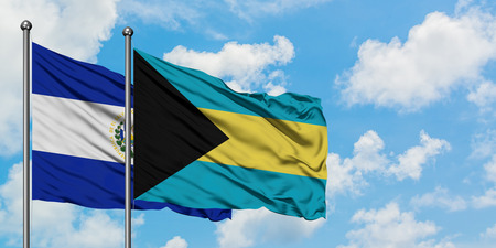El Salvador and Bahamas flag waving in the wind against white cloudy blue sky together. Diplomacy concept, international relations. Stock Photo - 123368823