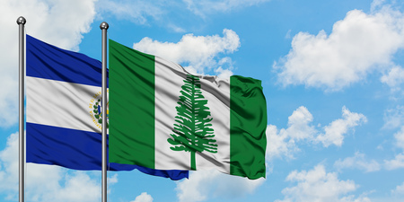 El Salvador and Norfolk Island flag waving in the wind against white cloudy blue sky together. Diplomacy concept, international relations.