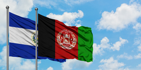 El Salvador and Afghanistan flag waving in the wind against white cloudy blue sky together. Diplomacy concept, international relations.