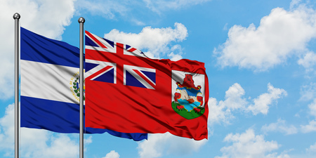 El Salvador and Bermuda flag waving in the wind against white cloudy blue sky together. Diplomacy concept, international relations.
