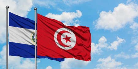El Salvador and Tunisia flag waving in the wind against white cloudy blue sky together. Diplomacy concept, international relations. Фото со стока
