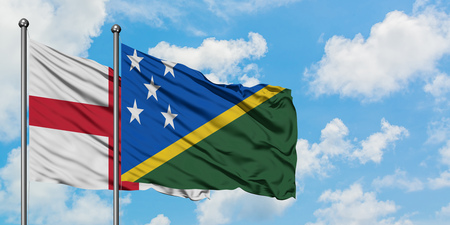 England and Solomon Islands flag waving in the wind against white cloudy blue sky together. Diplomacy concept, international relations. Stok Fotoğraf