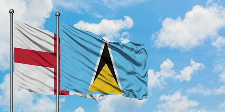 England and Saint Lucia flag waving in the wind against white cloudy blue sky together. Diplomacy concept, international relations.