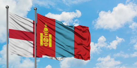 England and Mongolia flag waving in the wind against white cloudy blue sky together. Diplomacy concept, international relations. Foto de archivo