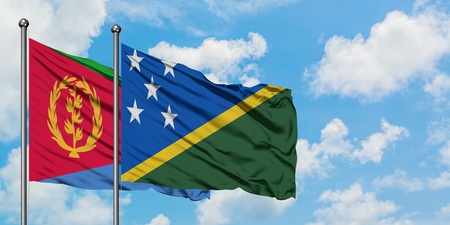 Eritrea and Solomon Islands flag waving in the wind against white cloudy blue sky together. Diplomacy concept, international relations.