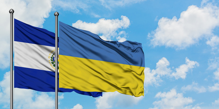 El Salvador and Ukraine flag waving in the wind against white cloudy blue sky together. Diplomacy concept, international relations.