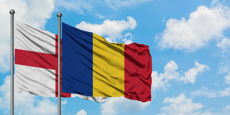 England and Romania flag waving in the wind against white cloudy blue sky together. Diplomacy concept, international relations.
