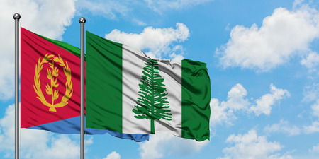 Eritrea and Norfolk Island flag waving in the wind against white cloudy blue sky together. Diplomacy concept, international relations. Stock Photo