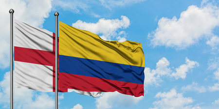 England and Colombia flag waving in the wind against white cloudy blue sky together. Diplomacy concept, international relations.