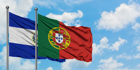 El Salvador and Portugal flag waving in the wind against white cloudy blue sky together. Diplomacy concept, international relations. Stock Photo