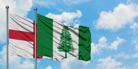 England and Norfolk Island flag waving in the wind against white cloudy blue sky together. Diplomacy concept, international relations.