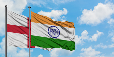 England and India flag waving in the wind against white cloudy blue sky together. Diplomacy concept, international relations.
