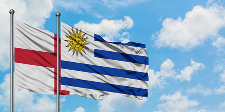 England and Uruguay flag waving in the wind against white cloudy blue sky together. Diplomacy concept, international relations. Banco de Imagens