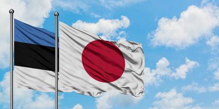 Estonia and Japan flag waving in the wind against white cloudy blue sky together. Diplomacy concept, international relations. Banco de Imagens