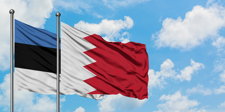 Estonia and Bahrain flag waving in the wind against white cloudy blue sky together. Diplomacy concept, international relations. Banco de Imagens