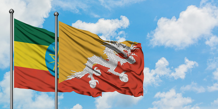 Ethiopia and Bhutan flag waving in the wind against white cloudy blue sky together. Diplomacy concept, international relations.