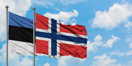 Estonia and Norway flag waving in the wind against white cloudy blue sky together. Diplomacy concept, international relations. Stock Photo