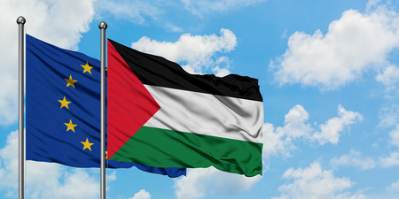 European Union and Palestine flag waving in the wind against white cloudy blue sky together. Diplomacy concept, international relations. Stock Photo