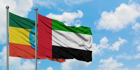 Ethiopia and United Arab Emirates flag waving in the wind against white cloudy blue sky together. Diplomacy concept, international relations. Stock Photo