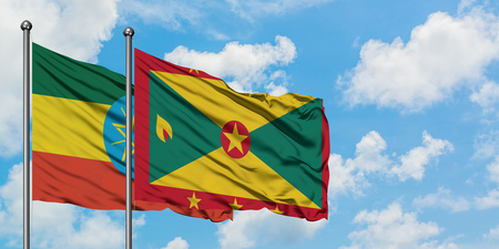 Ethiopia and Grenada flag waving in the wind against white cloudy blue sky together. Diplomacy concept, international relations.