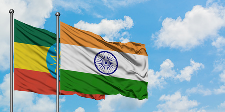 Ethiopia and India flag waving in the wind against white cloudy blue sky together. Diplomacy concept, international relations.