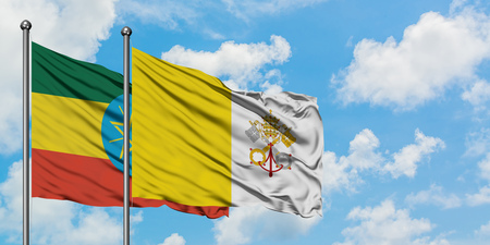 Ethiopia and Vatican City flag waving in the wind against white cloudy blue sky together. Diplomacy concept, international relations. 版權商用圖片