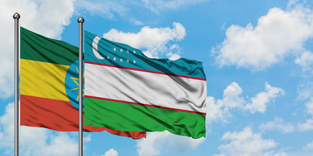 Ethiopia and Uzbekistan flag waving in the wind against white cloudy blue sky together. Diplomacy concept, international relations.
