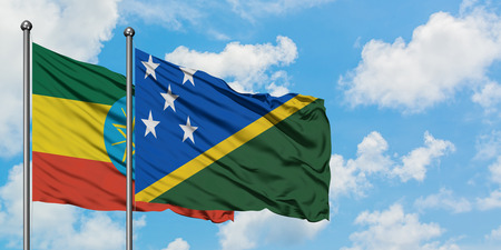 Ethiopia and Solomon Islands flag waving in the wind against white cloudy blue sky together. Diplomacy concept, international relations.