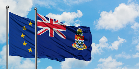 European Union and Cayman Islands flag waving in the wind against white cloudy blue sky together. Diplomacy concept, international relations. Stock Photo